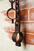 stock photo of shackles  - Old rusty shackles on a brick wall - JPG