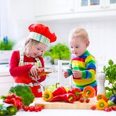 picture of twin baby girls  - Two little children adorable toddler girl in red chef hat and apron and funny baby boy preparing healthy lunch making delicious salad with fresh vegetables and garden herbs in a white sunny kitchen - JPG