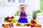 Cute curly little girl in a colorful summer dress eating fresh tropical fruit and berry