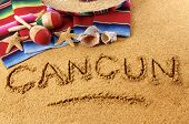 stock photo of mexican fiesta  - The word Cancun written in sand on a Mexican beach with sombrero straw hat traditional serape blanket starfish and maracas - JPG