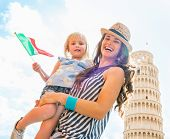 Portrait Of Happy Mother And Baby Girl With Italian Flag In Front Of Leaning Tower Of Pisa, Tuscany,