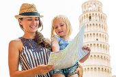 Happy Mother And Baby Girl Using Map In Front Of Leaning Tower Of Pisa, Tuscany, Italy