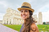 Portrait Of Happy Young Woman With Map On Piazza Dei Miracoli, Pisa, Tuscany, Italy