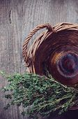 pic of wooden basket  - Brown glass pharmacy bottle and thyme herb in a wicker basket vintage style on old wooden board.