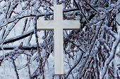 stock photo of storms  - Wooden cross hanging in branches of ice covered tree after ice storm