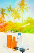 stock photo of uv-light  - Sun protection cream and sunglasses on palm beach background - JPG
