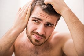 stock photo of male pattern baldness  - Handsome man is checking hairline while looking at the mirror - JPG