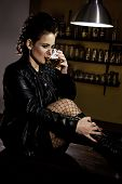 picture of peer-pressure  - Woman dressed in black leather jacket sitting on the bar and drinking alcohol - JPG