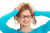 image of pulling hair  - Young angry teenager pulling her hair - JPG