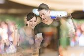 stock photo of mall  - Young Asian couple shopping and looking at cellphone in the mall - JPG