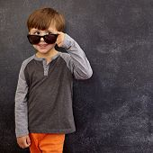 image of peer  - Portrait of a little boy in sunglasses looking at away at copy space - JPG