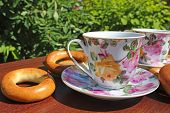 stock photo of bagel  - cup of tea standing on a wooden table and lie bagels - JPG
