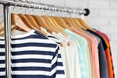 foto of clothes hanger  - Different clothes on hangers close up - JPG