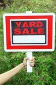 picture of yard sale  - Wooden Yard Sale sign in female hand over green grass background - JPG