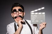 picture of moustache  - Young man with false moustache holding clapperboard isolated on gray - JPG
