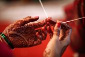 foto of hindu  - A religious thread held tight in the hands of a relative during a traditional hindu wedding ceremony - JPG