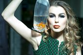picture of goldfish  - Winning young girl with bright makeup and blonde curly hair holding cellophane package aquarium with goldfish horizontal photo - JPG