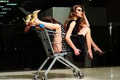 picture of trolley  - Two young misterious funny fashionable girls in dresses with shopping trolley indoor on store backdrop horizontal picture - JPG