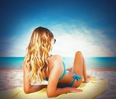 foto of sunbather  - Girl in bikini sunbathing at the beach - JPG
