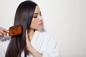 picture of hair comb  - beautiful young woman combing her healthy and shiny hair studio white - JPG