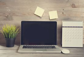 stock photo of wooden table  - Wooden working table with laptop and calendar - JPG