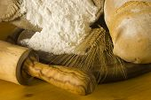 Detail of a rural kitchen with loaf of bread, wheat ears, white flour and rolling pin