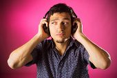Puzzled young guy listening music with headphones, pink background.