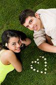 Jovem casal apaixonado, deitado em um pasto enquanto olha para câmera, forma do coração de Margarida na grama