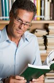 picture of reading book  - Mature man reading a book with glasses in a library - JPG