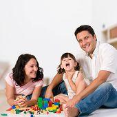Família feliz com os pais e filha brincando com blocos coloridos dentro, em casa