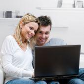 Jovem casal feliz, navegar na net com seu laptop em casa