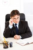 Authoritative business man sitting at office desk and straightening eyeglasses
