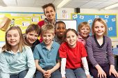 stock photo of school child  - School Children In Classroom With Teacher - JPG
