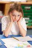 stock photo of school child  - Stressed Schoolgirl Studying In Classroom - JPG
