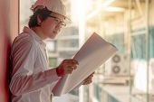 Engineer Or Architect Checking Architectural Drawing While Wearing A Personal Protective Equipment S poster