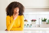 African american woman wearing yellow sweater at kitchen bored yawning tired covering mouth with han poster