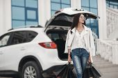 Beautiful Brunette Young Woman With Shopping Bag Near The White Super Car, Outdoors. Woman Standing  poster
