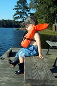 Boy Practices Safety On Fishing Dock
