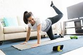 Beautiful Latin Young Woman Repeating Exercises While Watching Online Exercise Session On Her Smart  poster