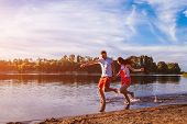 Young Man And Woman Running On Summer River Bank. Happy C Ouple In Love Having Fun At Sunset. Guys C poster