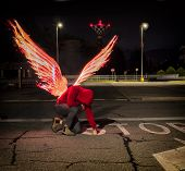 Fallen Male Angel Kneeling In City Parking Lot, With Fire Wings Spreading From His Back. Unrecogniza poster