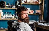 Man With Beard And Mustache Sits In Hairdressers Chair, Beauty Supplies On Background. Hipster With  poster