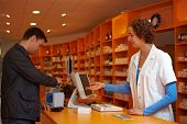 Customer In Pharmacy Paying With Card