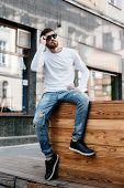 A Young Man Travels Through The Streets Of The City. Boy In Sunglasses Stylish Man Near The Building poster