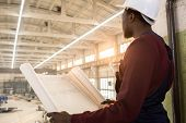 Rear View Of Pensive Purposeful Young African-american Construction Manager In Hardhat Holding Bluep poster