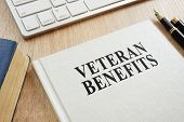 Book About Veteran Benefits On A Desk. poster