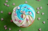 Cupcake With Whipped Cream And Pink Confectionery Sprinkling In The Form Of Hearts On Green Backgrou poster