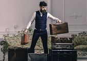 Luggage And Travelling Concept. Macho Elegant On Thoughtful Face Standing Near Pile Of Vintage Suitc poster