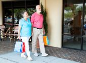 Senior couple shopping together at an outdoor mall.