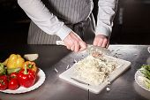 Closeup Of Hand With Knife Cutting Fresh Vegetable. Young Chef Cutting Beet On A White Cutting Board poster